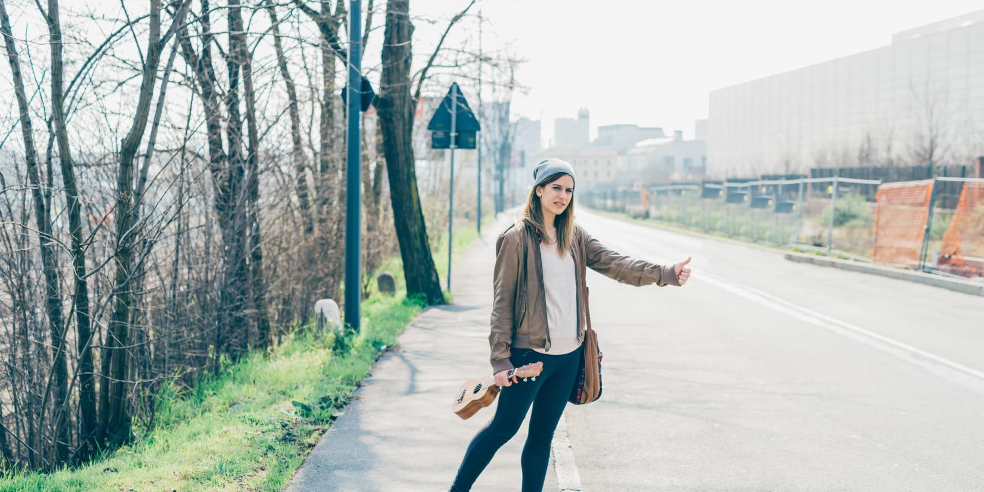 graphicstock-full-length-of-young-beautiful-caucasian-musician-woman-hitch-hiking-outdoor-in-the-city-holding-ukulele-traveler-music-transport-concept_rpgspoAtkb-1920×960